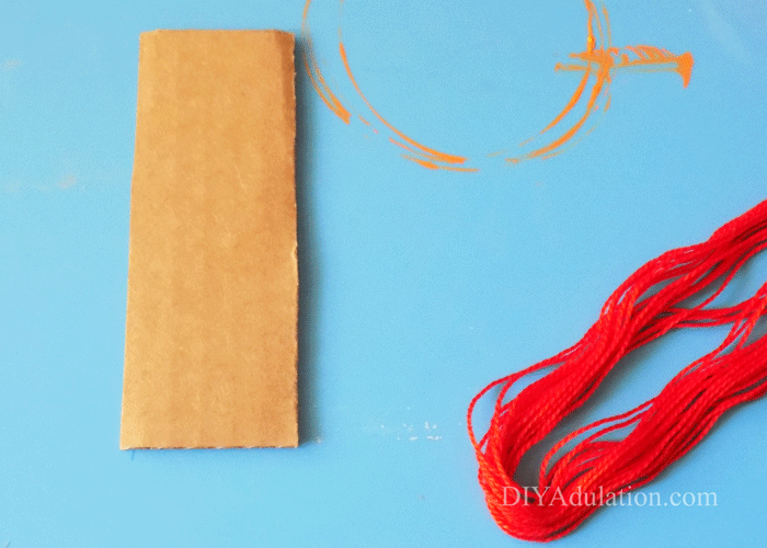 Piece of Cardboard and red DMC floss