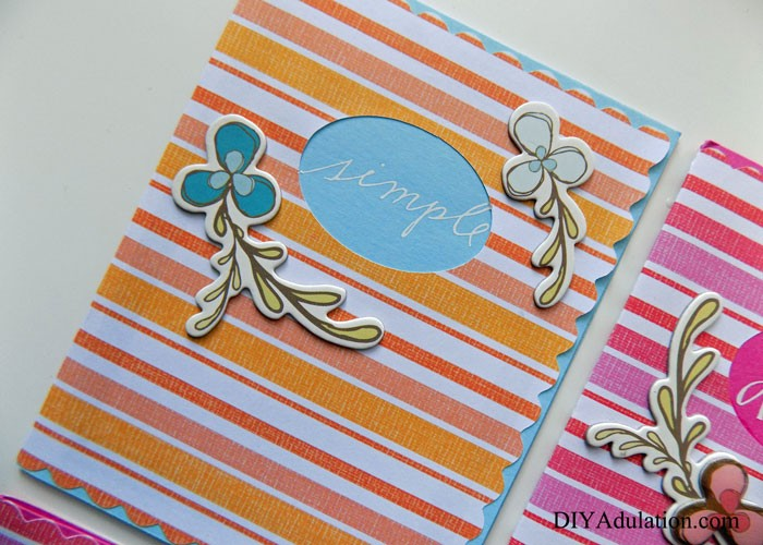 Close up of Simple Orange Striped Greeting Card with Flower Embellishments on the Front