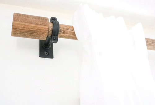 Wooden curtain rod close up in metal bracket on the wall
