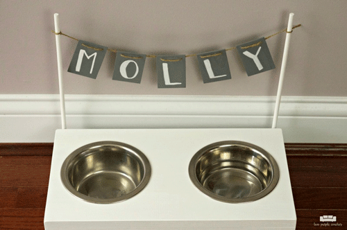 White dog bowl stand with attached banner that says Molly
