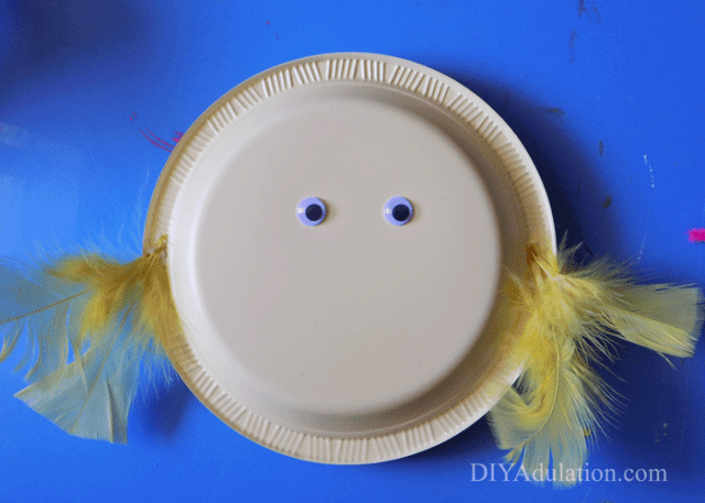 Yellow plastic plate with feathers glued to the sides and 2 googly eyes
