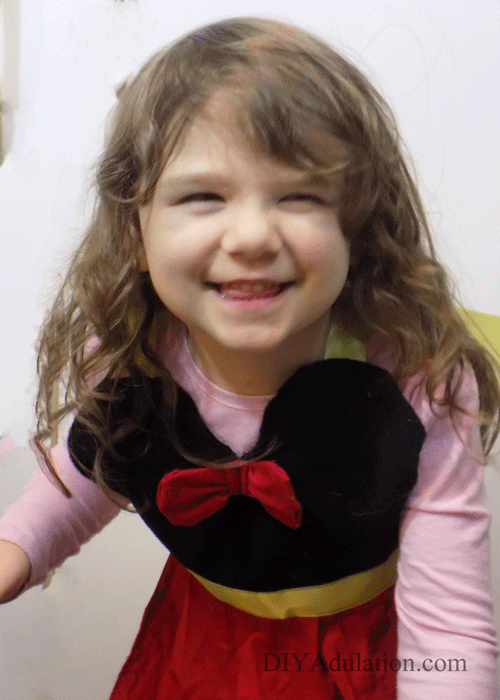 Little girl smiling and wearing Minnie Mouse apron