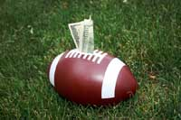 college football with money representing sports scholarships