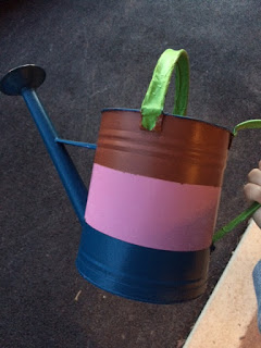 Using painters tape to paint a watering can red, white, and blue.
