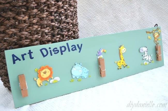 How to make an art display from leftover flooring. Cute zoo animal art display with clips to hold artwork or homework.