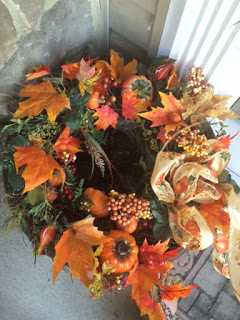 Using a wreath to decorate an empty planter to make Fall porch decor.