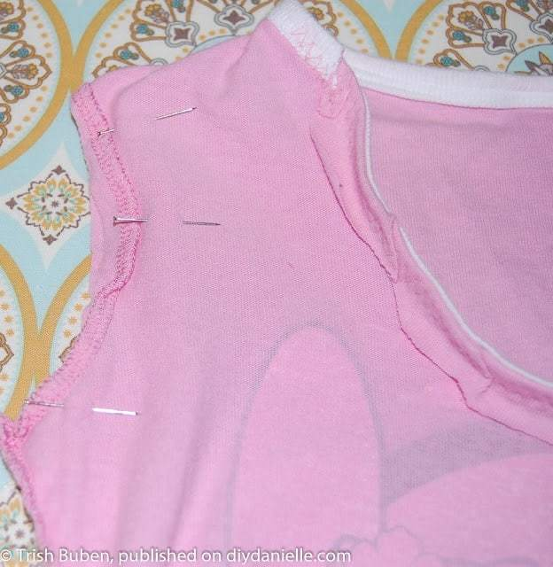 Sewing arm holes and bottom of shirt closed to make a tshirt clothespin bag.