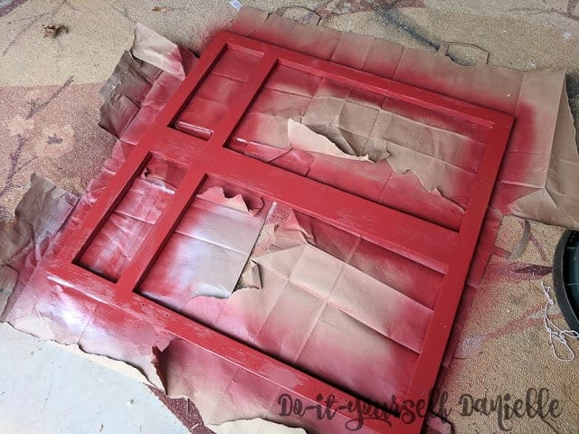 Spray painting the cabinet front red.