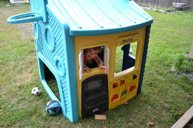 Kids space with a painted plastic playhouse.