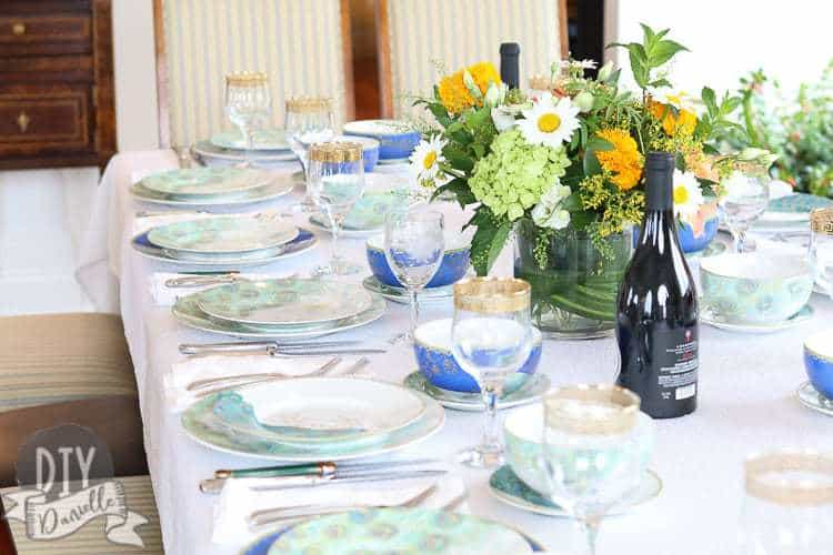 Peacock themed tablescape with a pop of color from the wine bottles and floral arrangement.