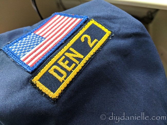 Den number patch, sewn on with a zig zag stitch and a sewing machine.