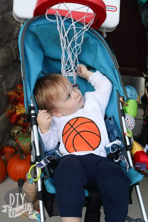 Baby as a basketball in a stroller that has a basketball hoop attached. Swoosh!