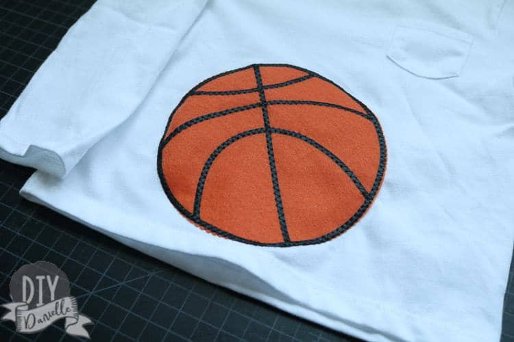 Basketball on the tummy area of baby's shirt.