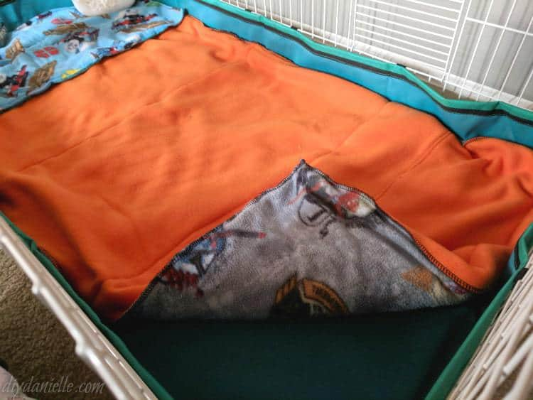 Handmade guinea pig cage liner with orange fleece on the top.