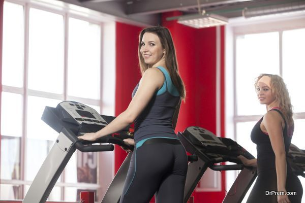 Two sporty girls in sportswear walking on cardio trainer, treadmill in gym