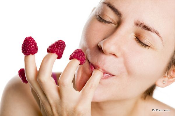 Young woman eating raspberries from fingers.