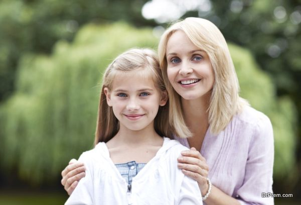 Portrait of a beautiful mature mother embracing her cute smiling daughter in the garden