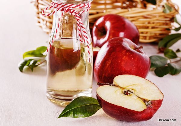 Apple cider vinegar and apples over white wooden background