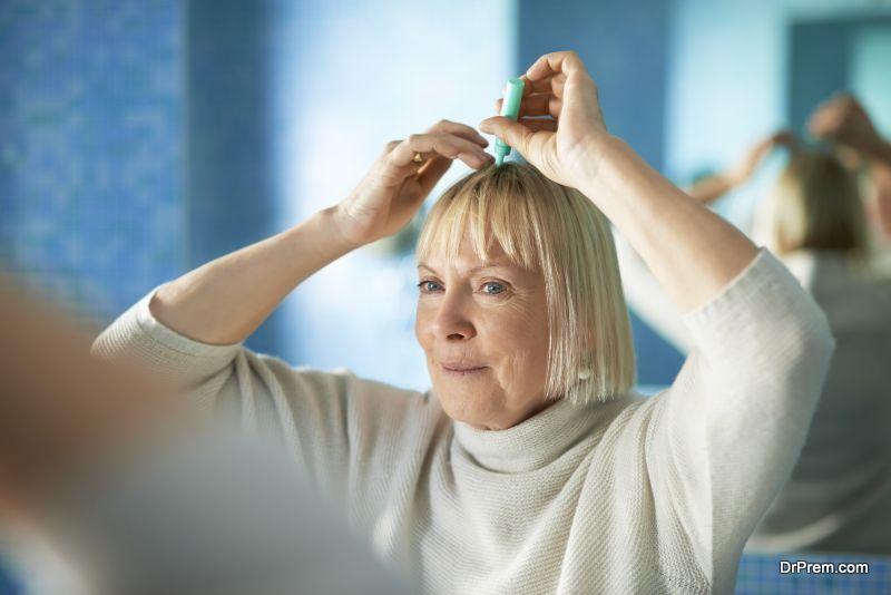 senior woman checking hairline in bathroom