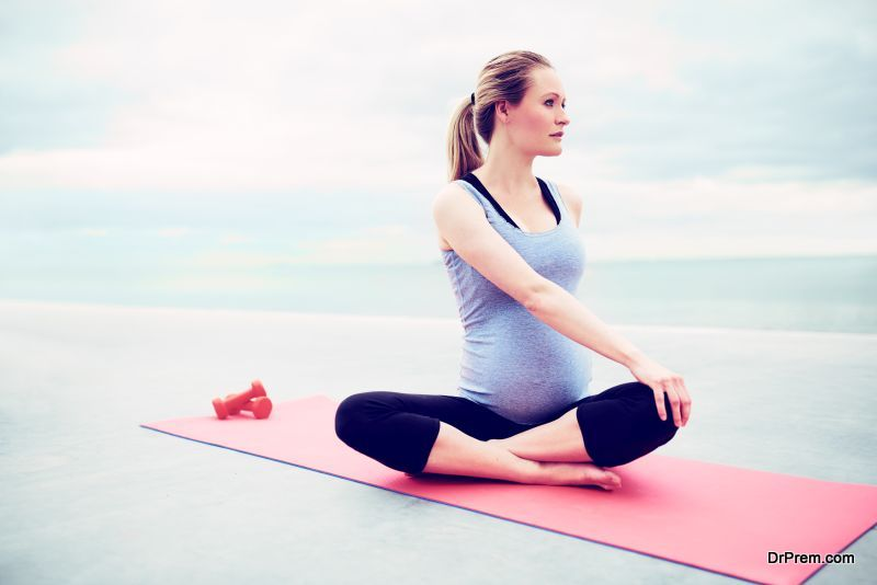 Pregnant young woman doing fitness exercises