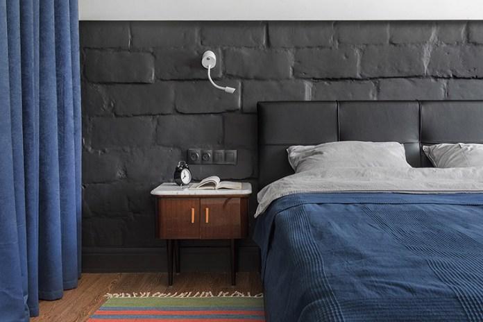Apartamento urbano/industrial. Cabeceira de couro sintético. Parede com blocos de concreto pintados de preto.