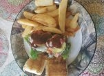 Two venison cheesburger sliders topped with white cheddar cheese, garden-fresh lettuce, bacon, and barbecue sauce.