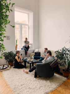 people gathered inside home house sitting on sofa