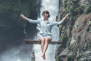 photo of woman riding swing in front of waterfalls
