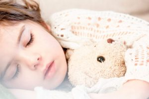 girl sleeping with her brown plush toy in guest bedroom