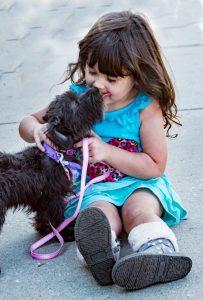 black dog beside little girl