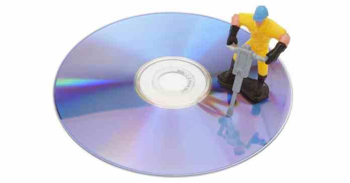 Cartoon mock up of a workman repairing a DVD with a jackhammer.