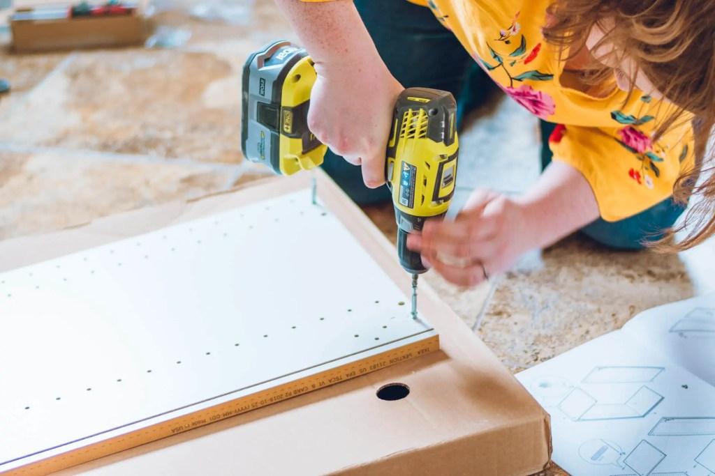 Catherine Ballard assembling an Ikea cabinet