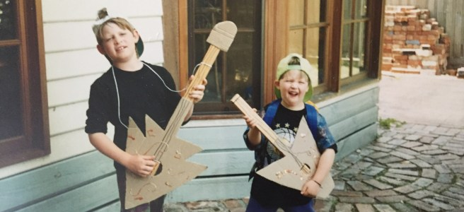 Two young boys playing cardboards guitars