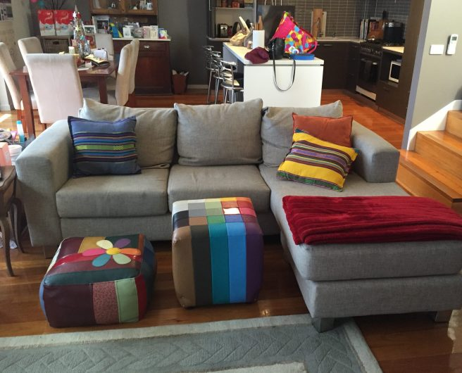 A living area with a couch covered in brightly coloured cushions