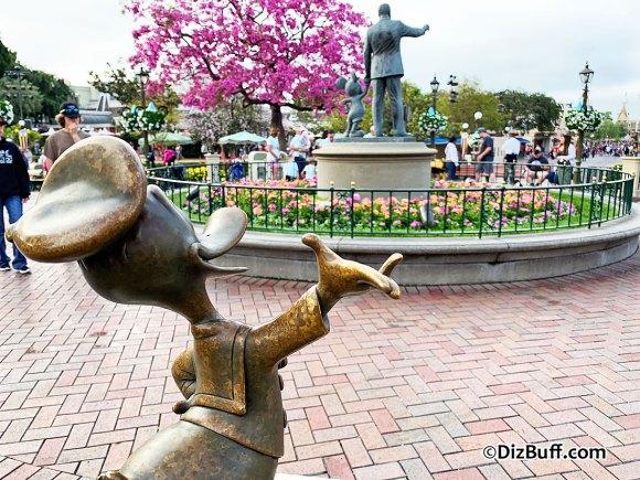 Donald Duck statue at the Hub Disneyland looking at Walt Disney Partners Statue