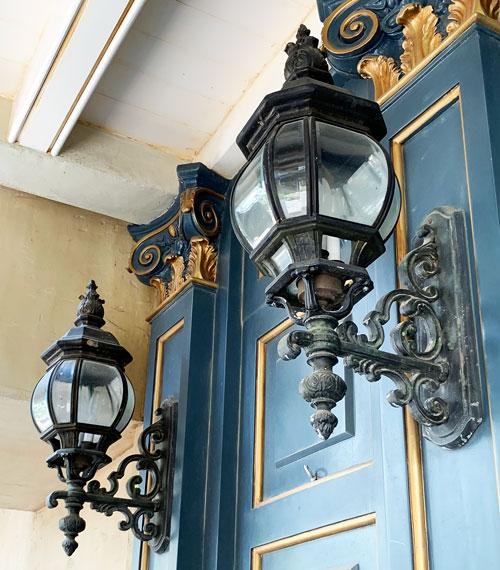 Two outdoor light fixtures on door of Cristal d'Orleans shop in New Orleans Square Disneyland
