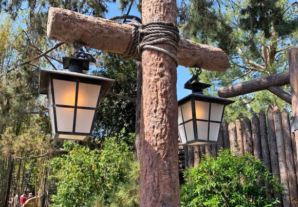 Double light fixtures hanging on tree trunks lashed together in Frontierland Disneyland