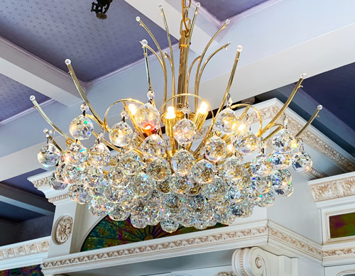 Clear crystal and gold chandelier hanging in La Mascarade d'Orleans Store in New Orleans Square Disneyland