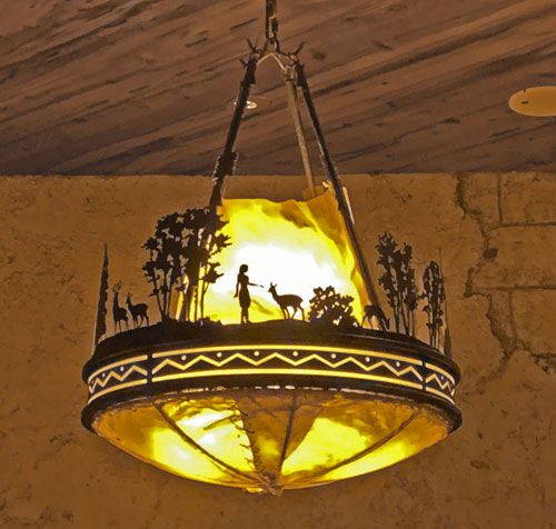 Close up of Old West ceiling light fixture depicting wildlife and trees in Pioneer Mercantile in Disneyland Frontierland