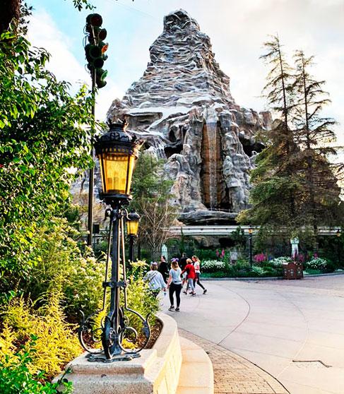 Ornate upright lamppost light fixture in view of The Matterhorn Mountain in Fantasyland Disneyland