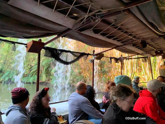 Disney guests cruise pass the backside of water on the Jungle Cruise attraction