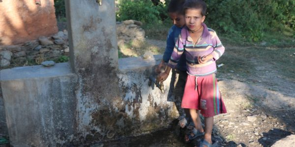 In Mellekh, Doti, a child uses a water tap.