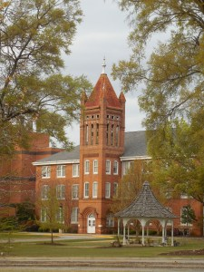 A three story red brick building with tower in front. Green lawn and trees. College campus.