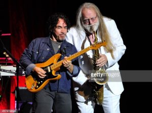John Oates and saxophonist Charlie DeChant jam together on stage