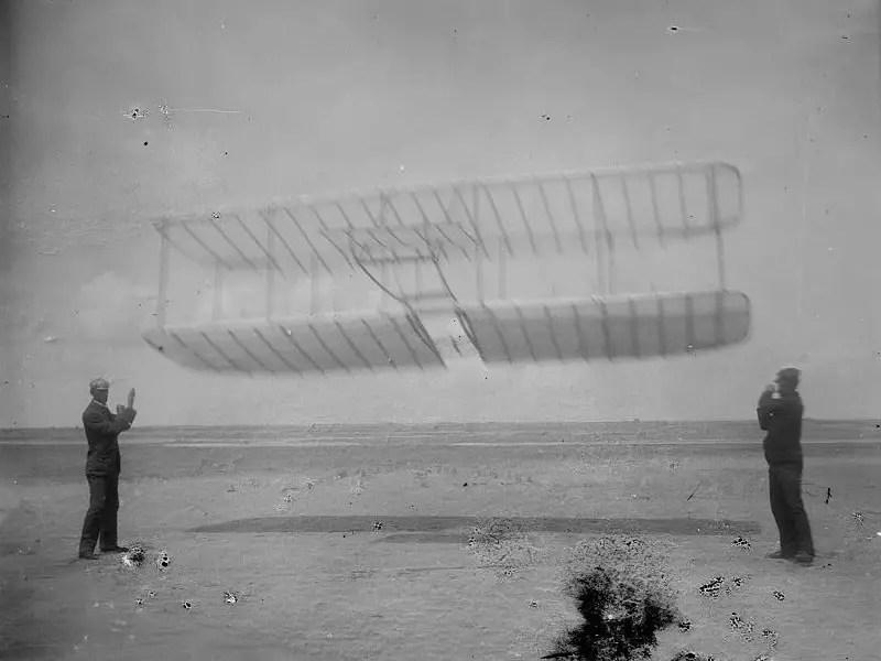 من اليسار إلى اليمين: (ويلبير)، طائرة (ذا رايت)، و(أورفيل) شقيقه، في (كيتي هاوك) في كارولاينا الشمالية سنة 1901.