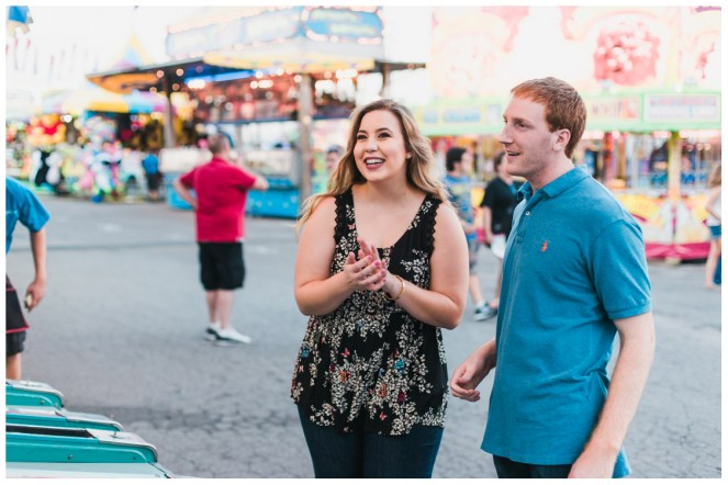 excitedly laughing playing skee ball - Carnival Engagement - Courtney and Alan