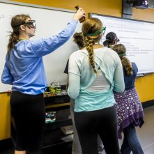 Students learn by collaborating to understand scientific theories, peer mentoring as they progress.