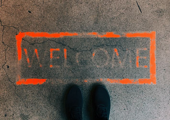 the word hello spraypainted in bright orange on a sidewalk with a pair of black shoes standing next to it