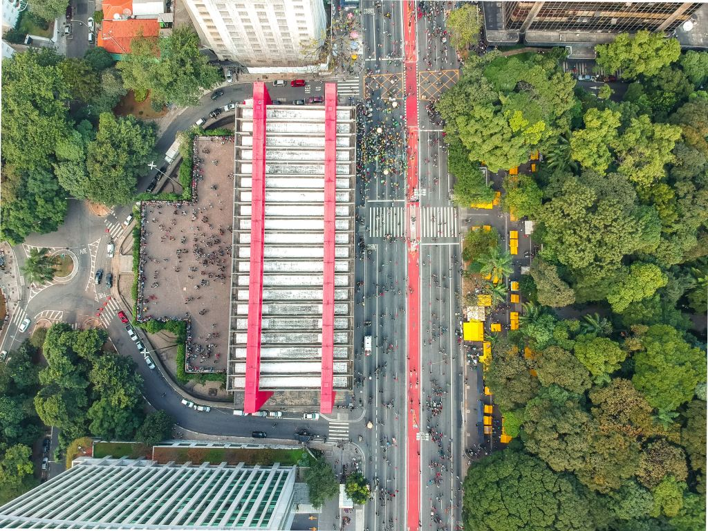 aerial photo of a city street with a red line painted down the middle, flanked by a building and a stand of trees