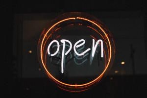 neon sign that says open in white letters against a black background